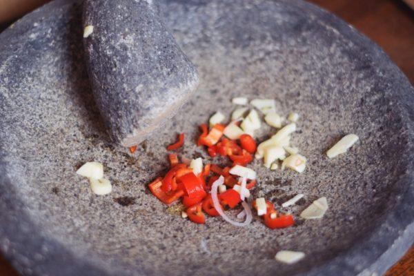 Chilis und Knoblauch fürs Dressing werden im Mörser zermahlen
